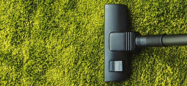 top view of cleaning green carpet with professional vacuum cleaner